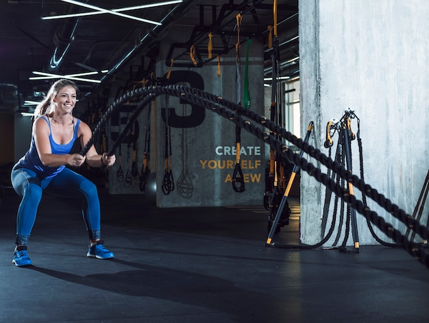 Fit woman exercising with battle ropes in fitness club