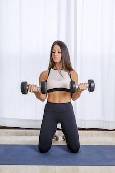 Подходит женщина, тренирующаяся с гантелями