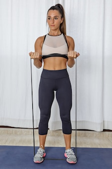 Fit woman exercising with resistance rope