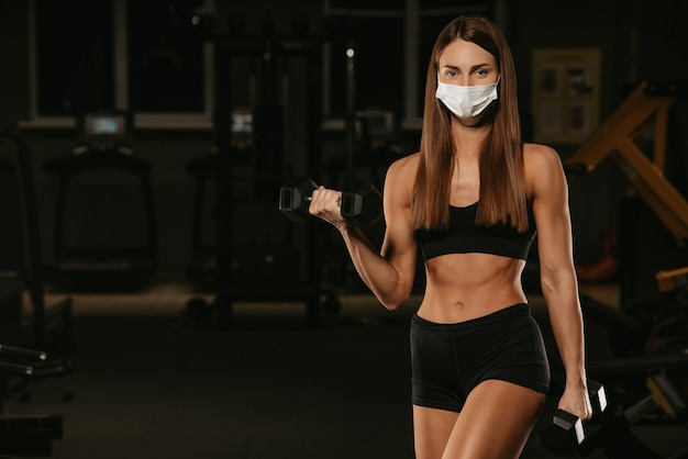 A fit woman in a face mask to avoid the spread of coronavirus is doing bicep curls with dumbbells. a sporty girl in a surgical mask is posing during the arms workout in the gym.