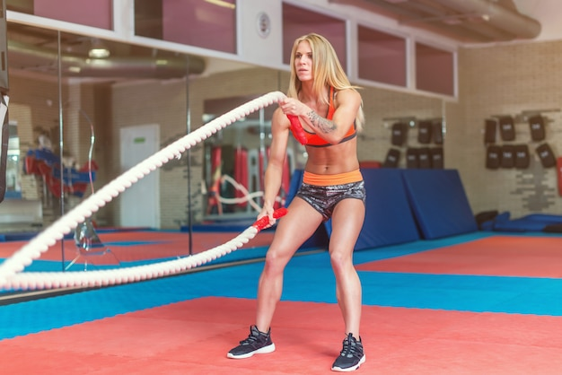 ジムのトレーニングでロープと戦う女性フィットネスに合います。