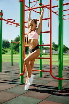 Fit woman hanging on ladder at sports ground