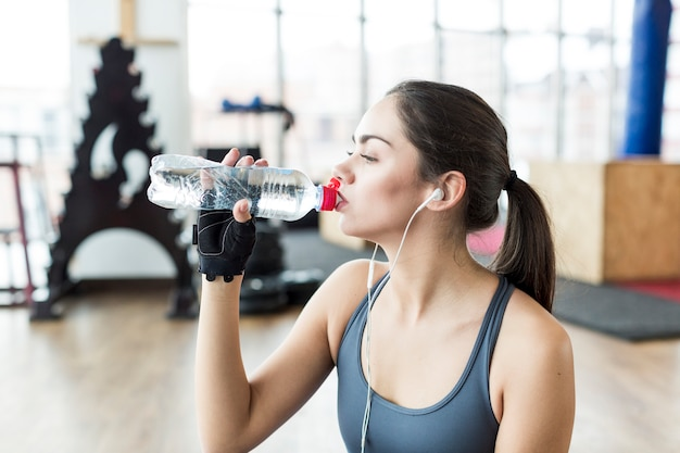 Fit woman in headphones drinking