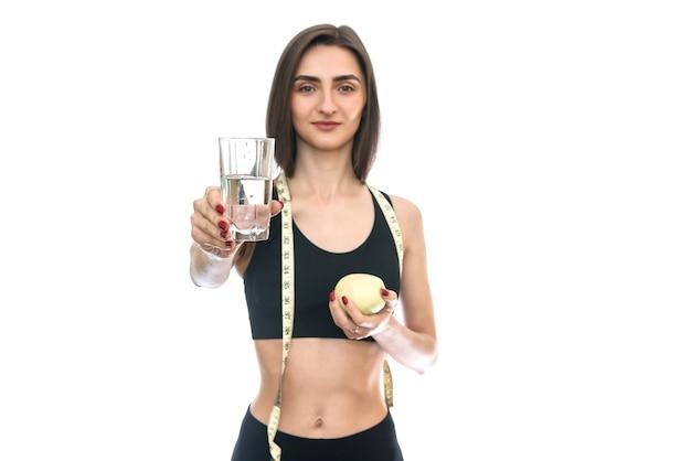 Подходит женщина, держащая яблоко и стакан воды, изолированные на белом