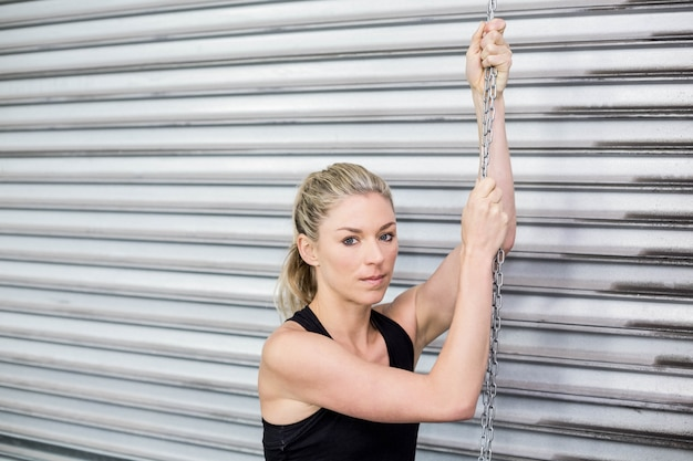 Fit woman holding chain at crossfit gym