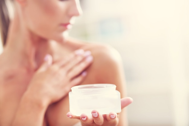 Fit woman holding lotion over her body