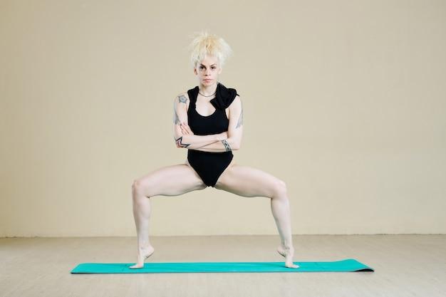댄스 수업 전에 워밍업을 위해 팁 발가락 스모 스쿼트를 하는 검은색 레오타드를 입은 여성
