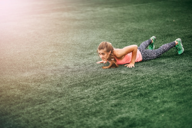 푸른 잔디에 burpees 할 밝은 스포츠 옷에 맞는 여자