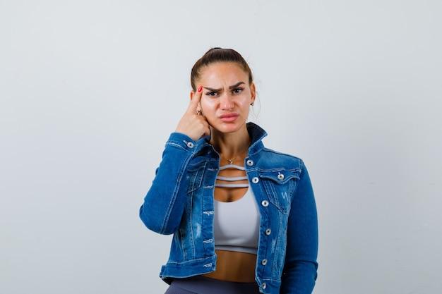 女性をクロップトップ、ジーンズジャケット、思考ポーズで立っているレギンス、こめかみに人差し指を置いて物思いにふける、正面図にフィットします。