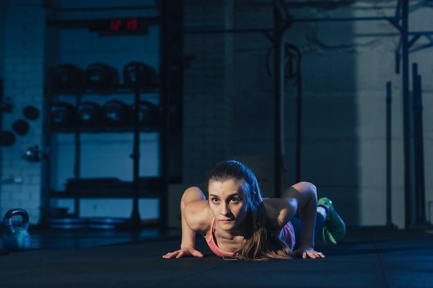 지저분한 산업 유형의 공간에서 보라색 운동 매트에 버피를하고 분홍색 다채로운 운동복에 맞는 여자
