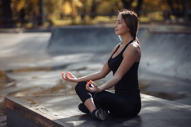 Подходящая женщина в спортивной одежде, практикующая лотос йоги в спортивном парке.