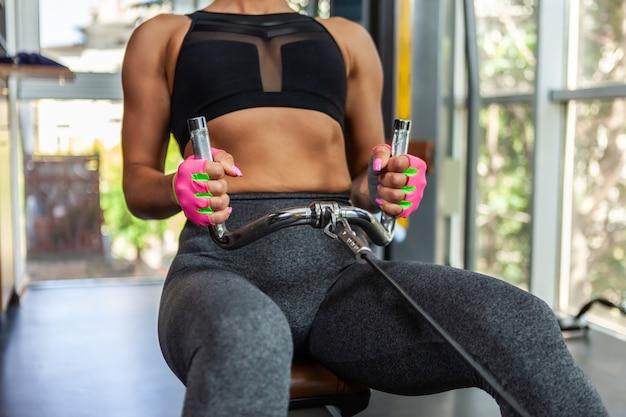 허리와 팔 근육을 위해 운동하는 밧줄 케이블 무게 기계를 당기는 운동복에 맞는 여자. 바디 빌딩 및 건강 개념입니다.