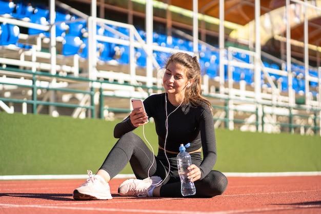トレーニングやランニングの後に休んでいるスポーツウェアに女性をフィットさせる