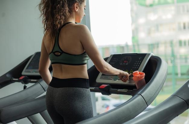 운동복에 맞는 여성은 러닝 머신에서 실행되며 체육관에서 시계를 봅니다. 건강한 라이프 스타일, 워밍업, 피트니스, 체중 감량의 개념.