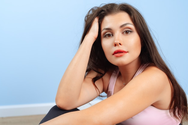 Подходит женщина в спортивной одежде, сидя на полу в тренажерном зале
