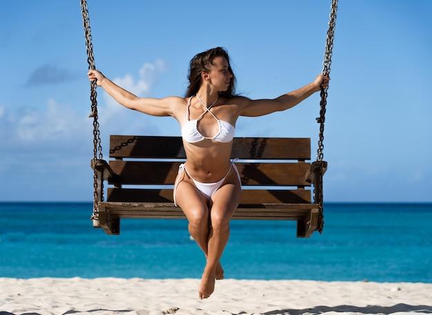 해변에 앉아 흰 비키니 입은 여자를 맞추고 평온한 휴가 및 레저의 일광욕 백사장과 맑은 푸른 바닷물 개념을 즐기십시오.