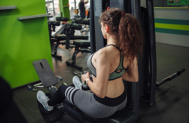 맞는 여자는 체육관에서 시뮬레이션 로잉 머신 훈련