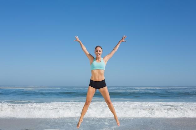 ビーチで腕を振ってジャンプする女性にフィット