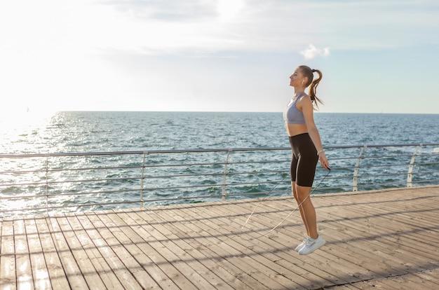 Подходит женщина, прыжки через скакалку на пляже на рассвете