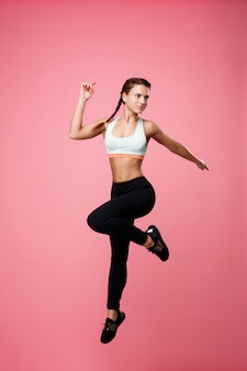Fit woman jumps holding left hand back pointing with finger