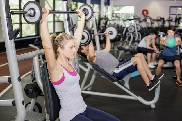 Fit woman lifting barbell in crossfit gym