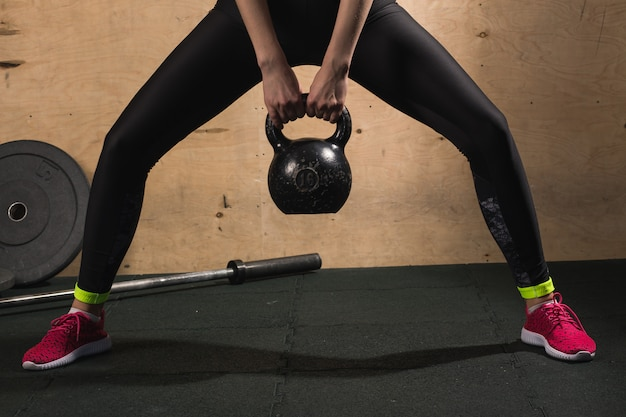 Fit woman lifting heavy weight kettle bell at gym