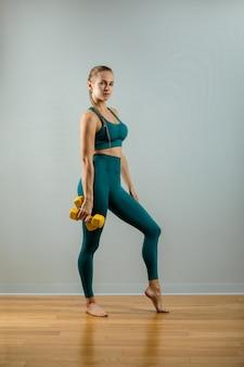 ウェイトトレーニングをフィットの女性。灰色の背景にダンベルでポーズ灰色の背景に美しいフィットネス女の子。