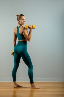Fit woman lifting weights beautiful fitness girl posing with dumbbells