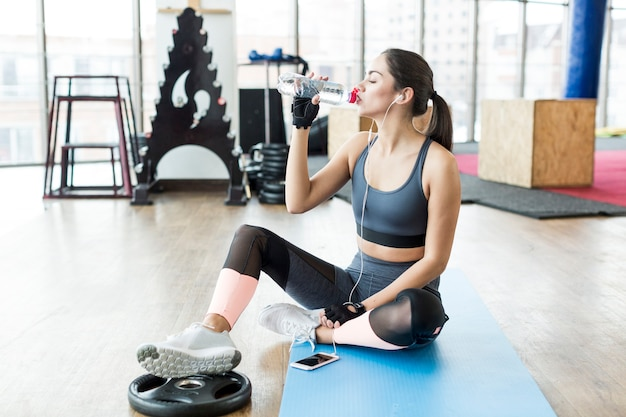 Fit woman listening to music and drinking