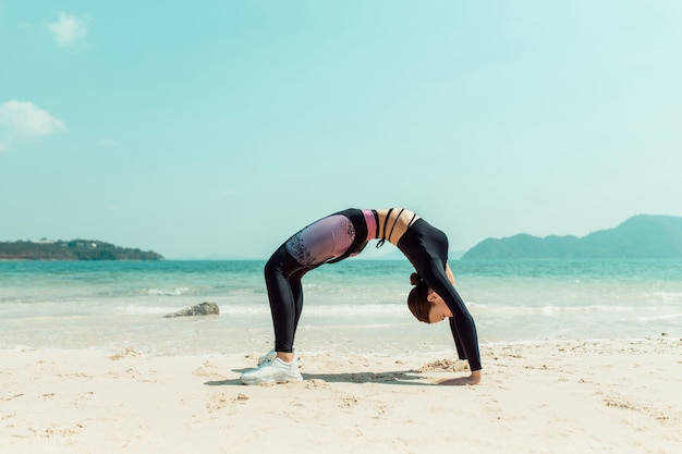 Fit woman making stretching gymnastic at the beach. beautiful woman doing yoga in the hot summer day. phuket. thailand