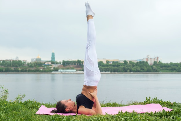 Fit woman making yoga in shoulderstand pose exercising in nature