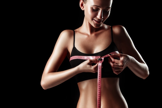 The fit woman measuring perfect shape of beautiful body. healthy lifestyles concept
