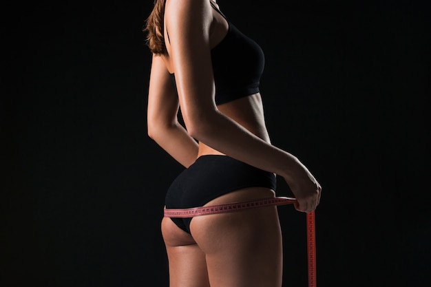 The fit woman measuring perfect shape of beautiful figure. healthy lifestyles and fitness concept