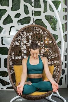 掛かる椅子で瞑想する女性に合う
