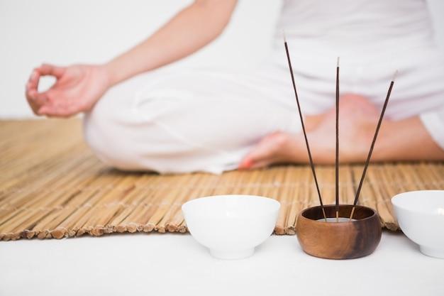 Подходящая женщина, медитирующая на бамбуковый коврик