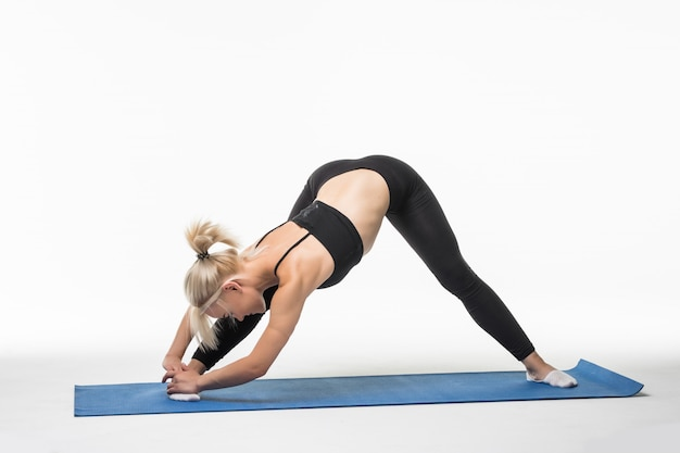 Fit woman model doing stretching exercises on the floor in the studio on white