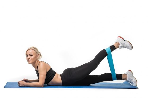 白のスタジオの床でストレッチ体操を行う女性モデルに合わせて