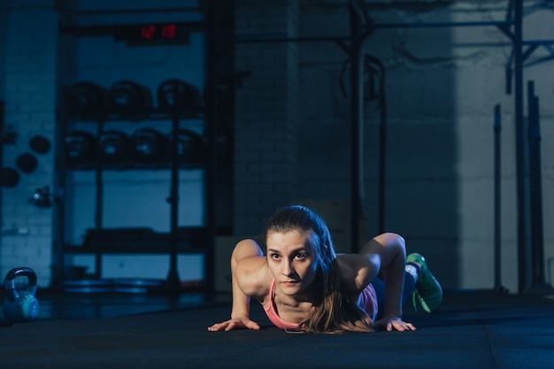 Fit woman in pink colourful sportswear doing burpees on a purple exercise mat in a grungy industrial type space