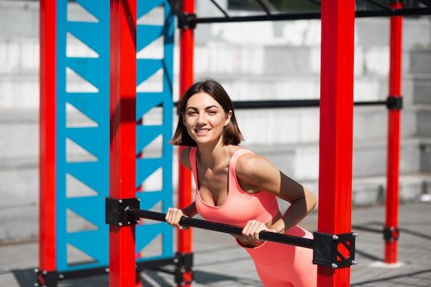 Donna in forma in abbigliamento sportivo rosa aderente all'aperto fa flessioni sul bar