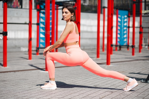 Fit woman in pink fitting sportswear outdoor stretching herself