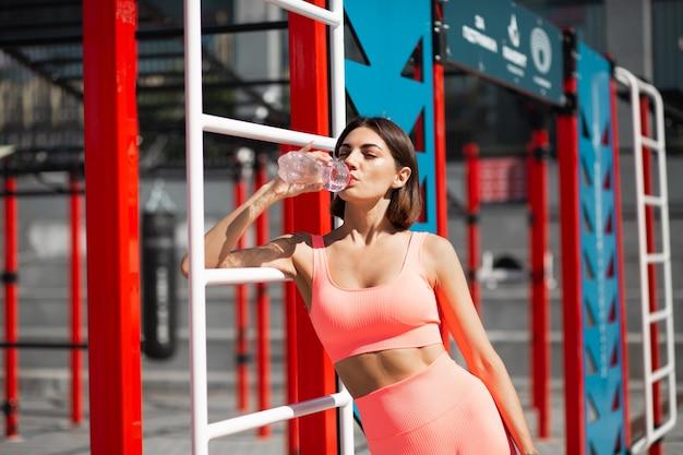 Donna adatta in abbigliamento sportivo aderente rosa all'aperto con bottiglia d'acqua