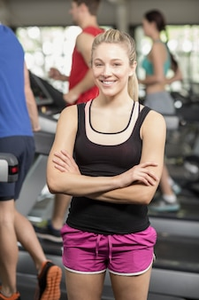 Fit woman posing with arms crossed at gym
