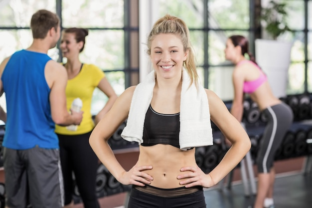 Fit woman posing with athletic women and man behind at crossfit gym