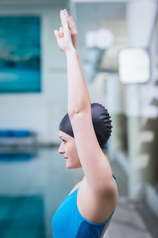 Fit woman raising arms at the pool
