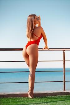 Fit woman in red bikini posing near the sea