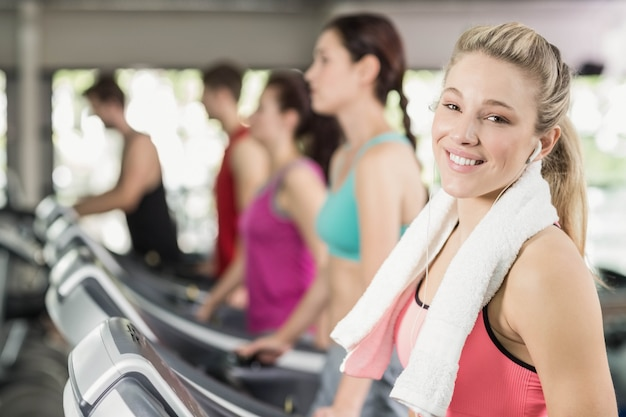 Fit woman running on the treadmill while listening music in crossfit