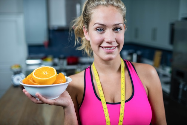 Fit woman showing a bowl of oranges in the kitchen