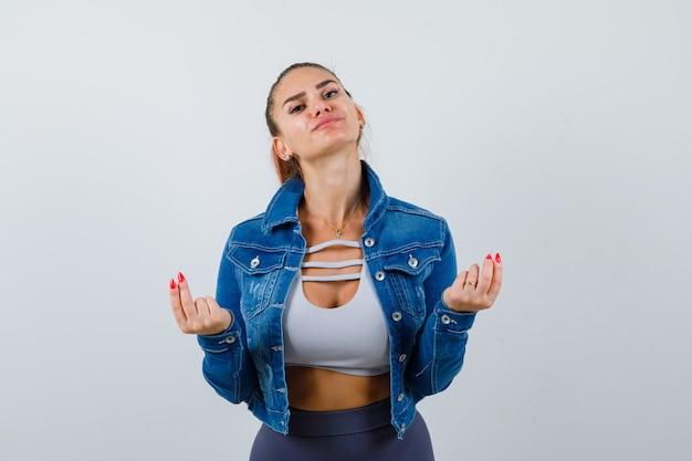 クロップトップ、ジーンズジャケット、レギンスでお金のジェスチャーを示し、自信を持って見えるフィットの女性、正面図。
