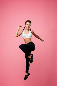 Fit woman in sport clothing jumping with left leg up