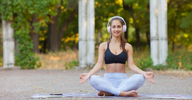 Fit woman in sports clothes sitting in lotus pose in the park and listening to music on headphones.  healthy lifestyle. yoga and relax concept.